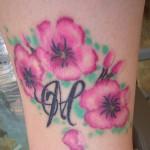 Modèle de tatouage fleurs et initiale sur la cheville
