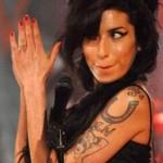 Tatouage d'Amy Winehouse sur le bras : pin up aux seins cachés et fer à cheval