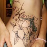 tatouage de fleurs et lézard sur la hanche